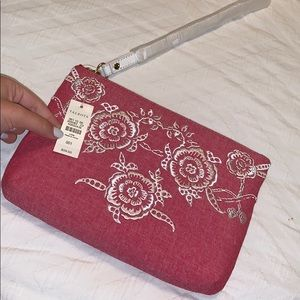 Pink wristlet bag with white strap